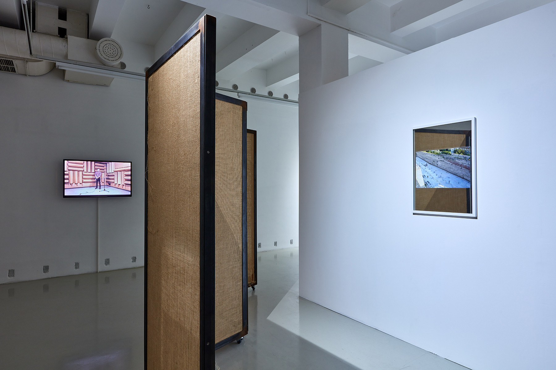 Exhibition view. On the left: Roman Štětina: Untitled (Speak so I can see you), 2020. installation (jute, iron, wood); On the right: Andreas Fogarasi: Mirrors - Car park of Buda castle during construction, Budapest, 2011. C-Print on mirror | photo: Dávid Biró